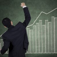 Successful businessman and financial graph on the wall